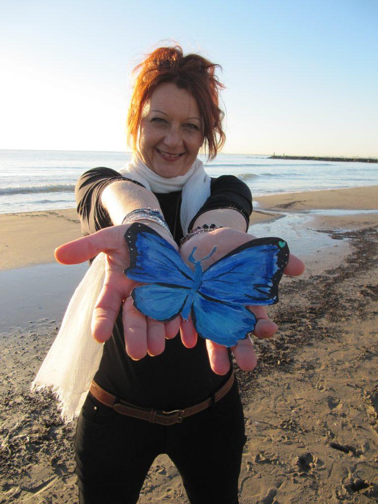 escritora Luz Ros con dibujo mariposa azul en las manos