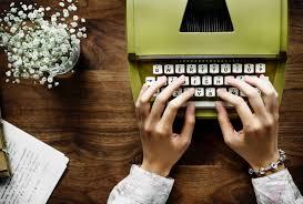 acción de manos escribiendo a máquina de escribir